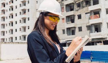 african american lady safety helmet with notepad near building construction
